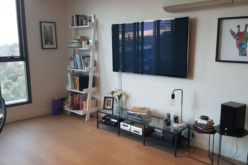 """Living room with 60"""" TV, sound system and playstation"""