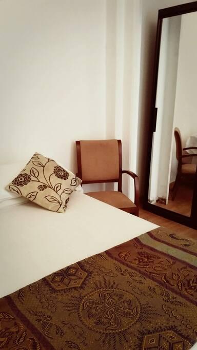 Habitacion Especial para parejas, tiene velador con lámpara ,silla y armario con espejo
