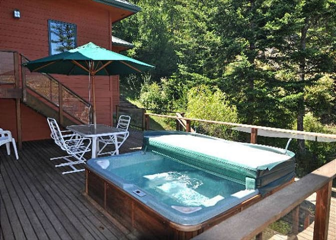 There is a large hot tub that is located on a side deck.