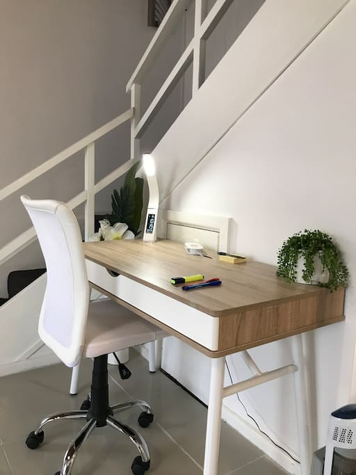 Large office workspace with desk lamp and charging station at your fingertips.