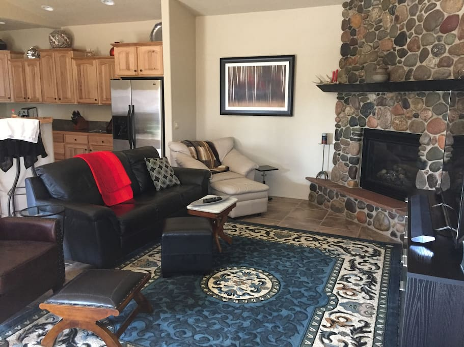 open floor plan with gas fireplace, large flat screen TV, and plenty of seating