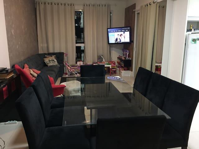 Sala de estar e sala de jantar com acesso à cozinha e varanda com churrasqueira e vista do mar.
