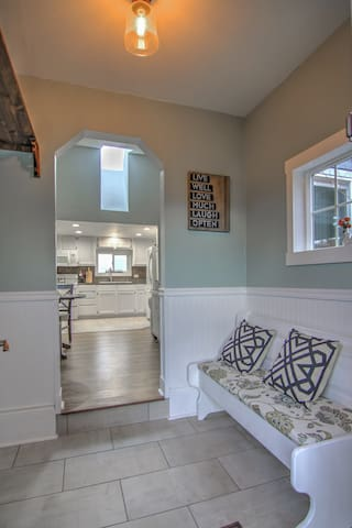 Entryway includes storage shelf and sitting bench.
