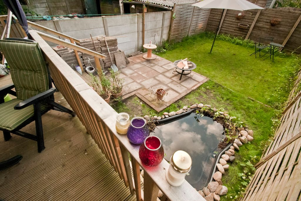 Big garden with a roofed veranda, a cute pond with fish, cosy firepit and enough seating areas.