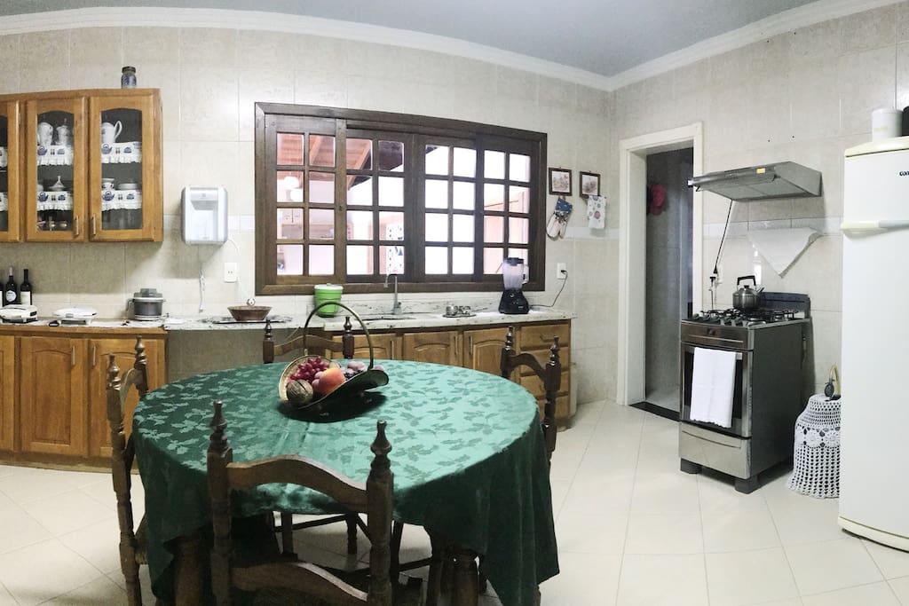 Cozinha grande com fogão elétrico e exaustor, geladeira, armários, pia, água filtrada, fogão de chapa à gás (semelhante ao fogão à lenha), mesa para 4-6 lugares.