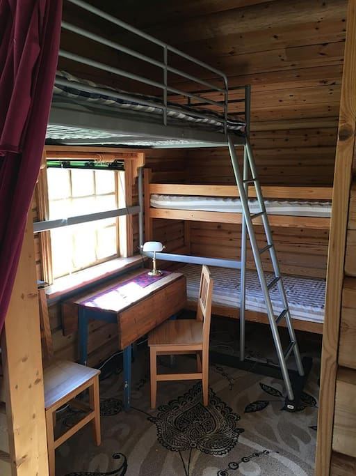 Bed room with 3 bunk beds and a working space area next to the window.