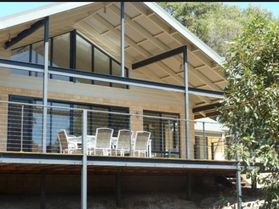 North facing deck with 10 seater table, two comfortable outdoor chairs and side table, and a gas BBQ with hood.
