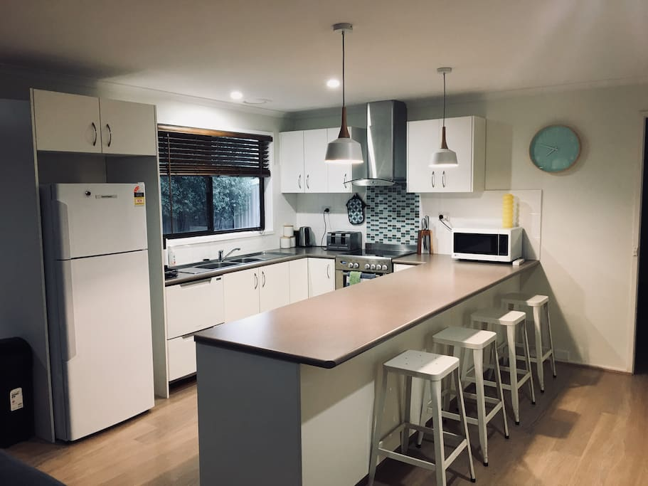 Modern Kitchen with double drawer dishwasher, pod coffee machine, microwave, kettle, 4 slice toaster, fan forced electric oven and ceramic cooktop, quality pots and pans, ample kitchenware and crockery.