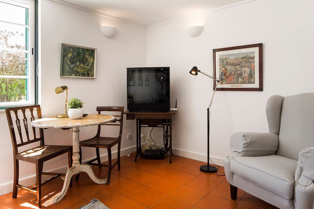 Sala,canto com TV e mesa.