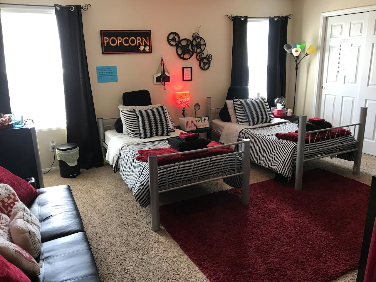 Cute converted large movie themed room with 2 twin beds and a futon that folds out into a twin makes comfortable sleeping for 3. Enjoy full cable with smart TV options, wifi and bottled waters from your personal mini fridge.