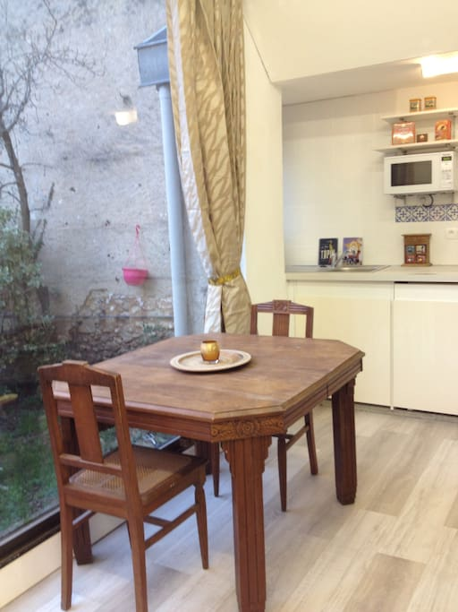 Well fitted kitchen and sitting area overlook private courtyard and views to Notre Dame