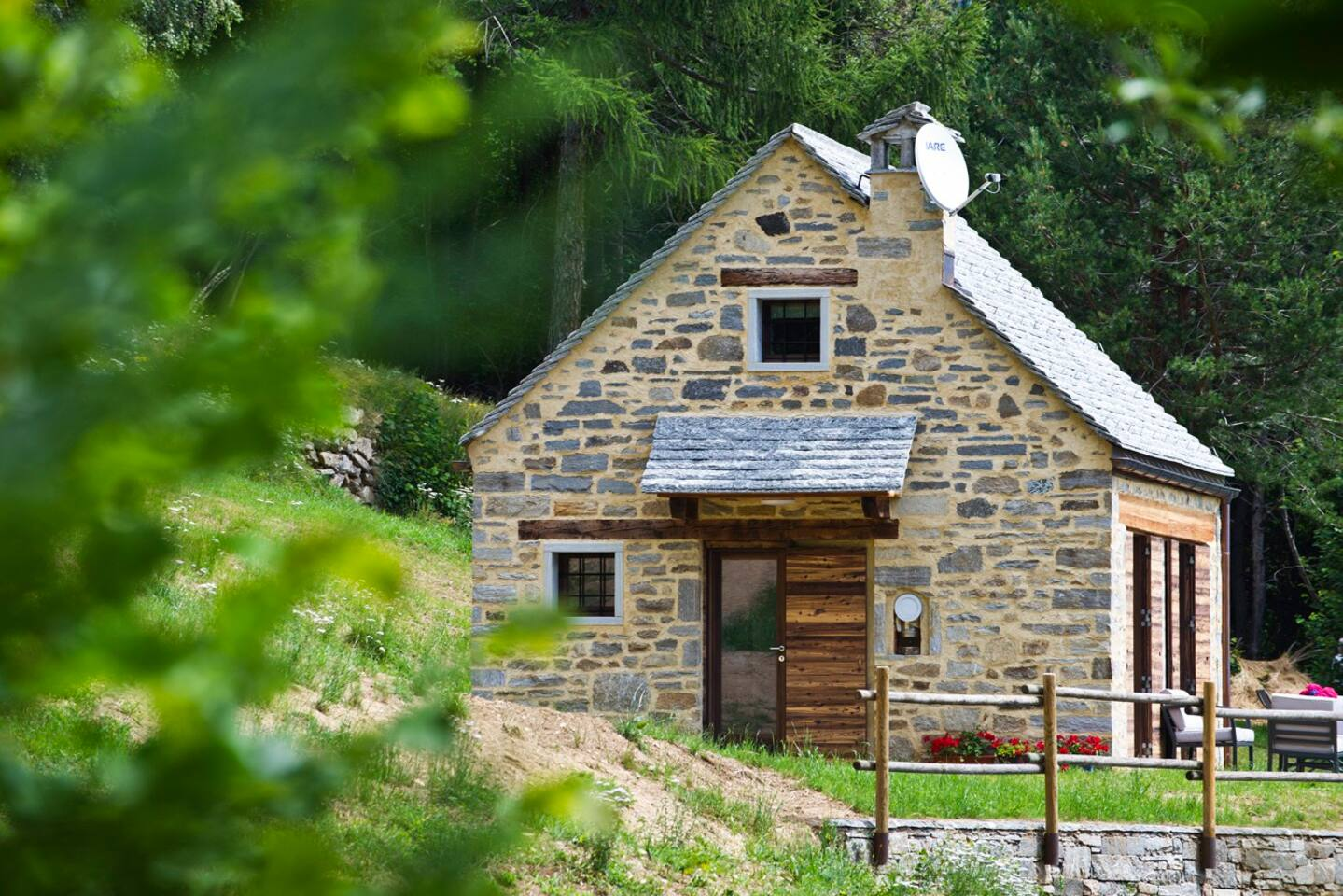 Completamente ricostruito su un rudere, lo chalet Milly in sasso con tetto in pietra e porte e finestre in legno naturale.