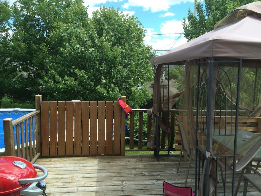 Balcon avec table, chaises, BBQ et piscine