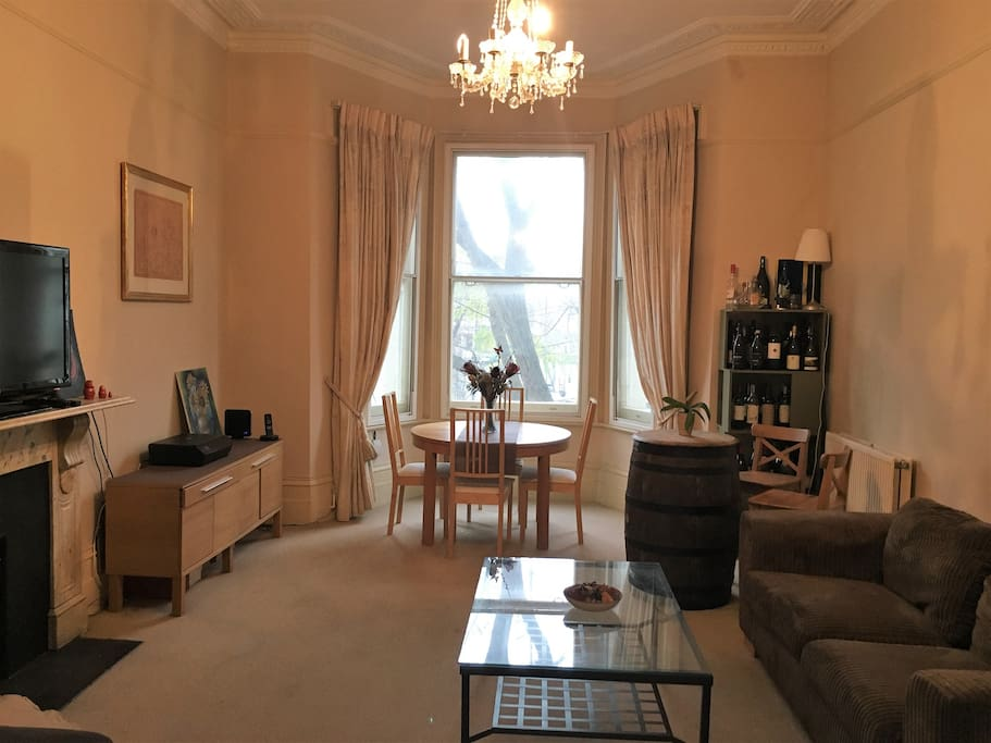 Bright living room with fireplace, blue sofabed, brown sofa and table that can sit 4-6 pax.