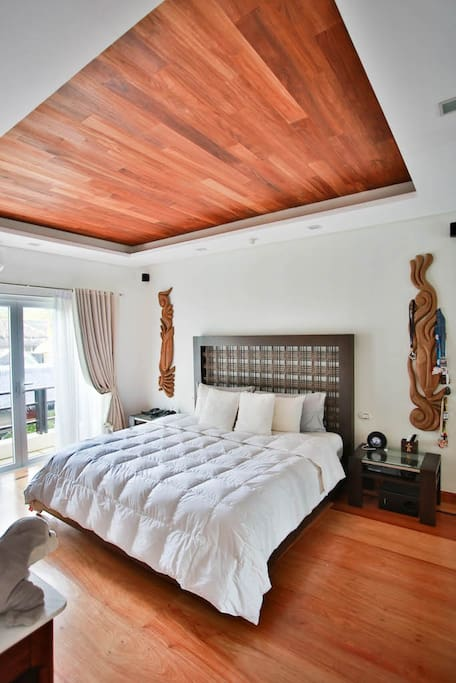 """The master bedroom, beautifully finished with prestigious hardwoods, 52"""" TV, bluetooth speakers and floor-to-ceiling mirrors, air-conditioning and little working desk. Ocean view from the balcony"""