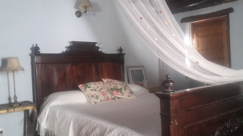 Habitació matrimoni amb bressol per a bebé.
