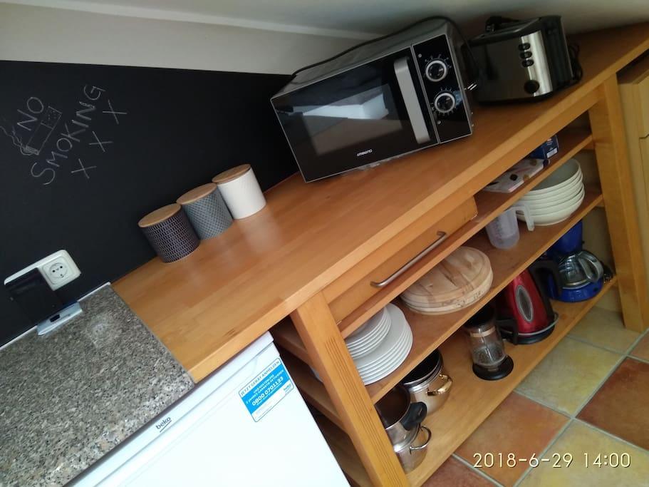 Mikrowelle, Toaster, Kaffee, Kaffeemaschine(Filtermaschine), Gewürze, Essig, Öl, Zucker, Salz, Pfeffer, Radio, Wasserkocher, Töpfe, Teller, Gläser, Weingläser, Kühlschrank, Gasherd, kleiner Überbleibsel-Schrank