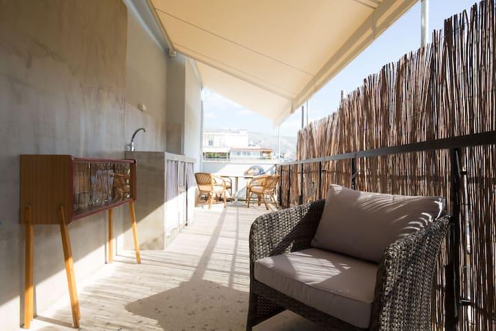 Terrasse mit praktischer Aussenküche, Electro-Grill, Waschmaschine, grosser Esstisch und Couchgarnitur