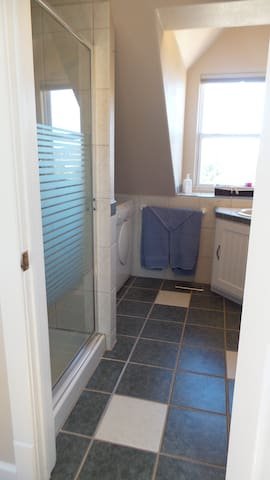 Tiled bathroom with guest size washer and dryer.