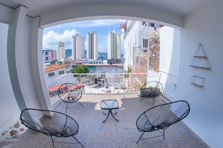 Terraza del acceso principal con sillas acapulco y una agradable vista.