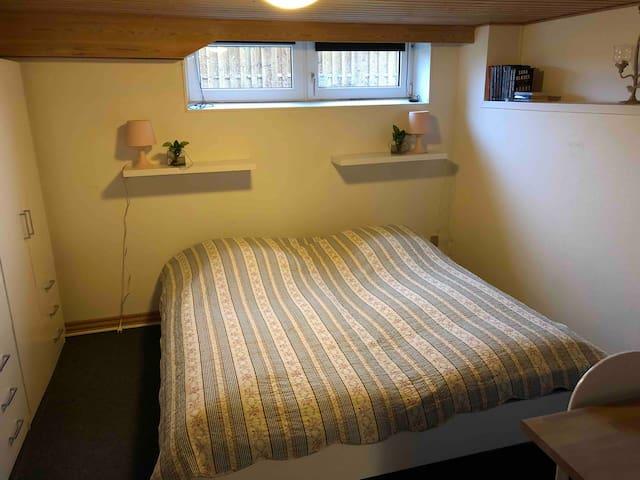 Lyst soveværelse med dobbeltseng og klædeskabe og skrivebord