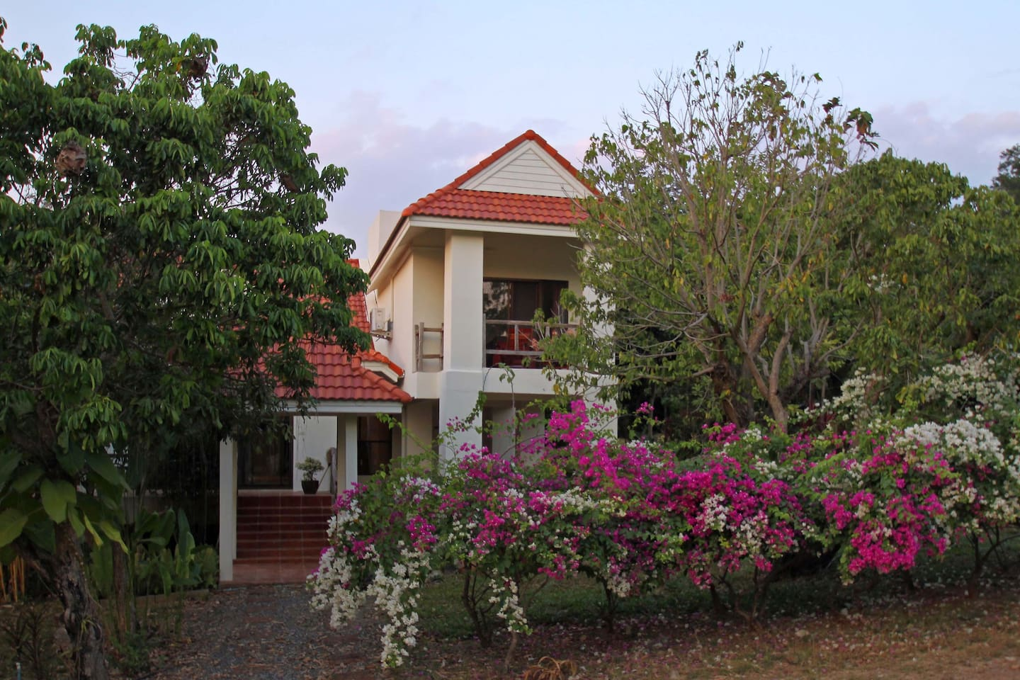 View from road towards house showing balcony of 1st floor bedroom. Magnificent bouganville has flowers most of the year. Longan fruit tree to the right, behind it is the main terrace.