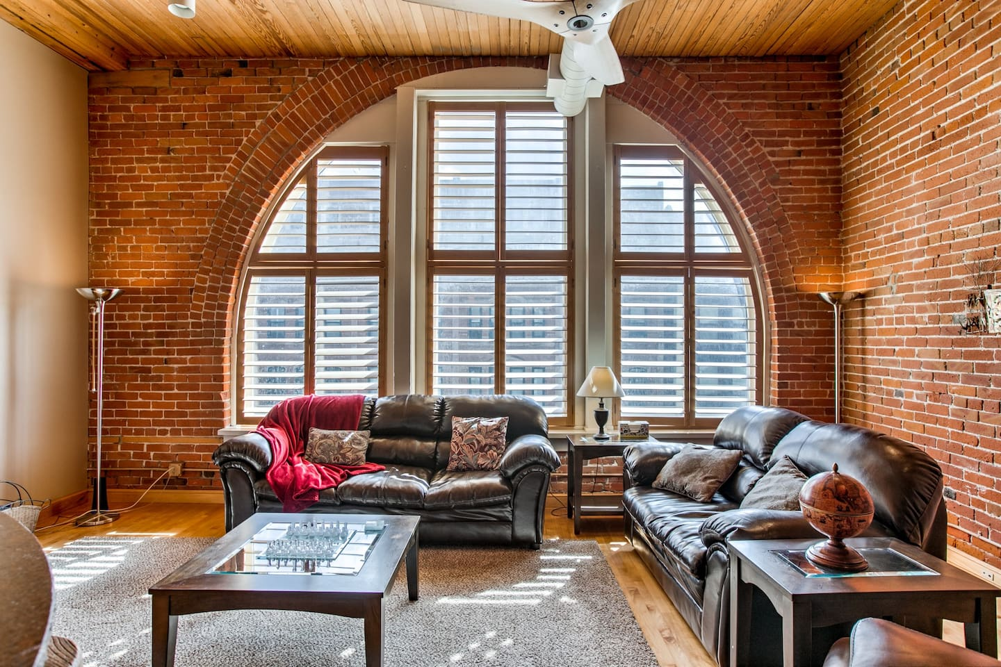 Living room, leather couches and recliner with the unique crescent shaped window that looks out to the Old Market with custom made shades