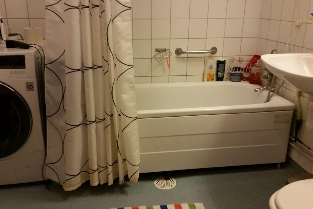 Badrum med wc, badkar och tvättmaskin. Halvkaklat.
