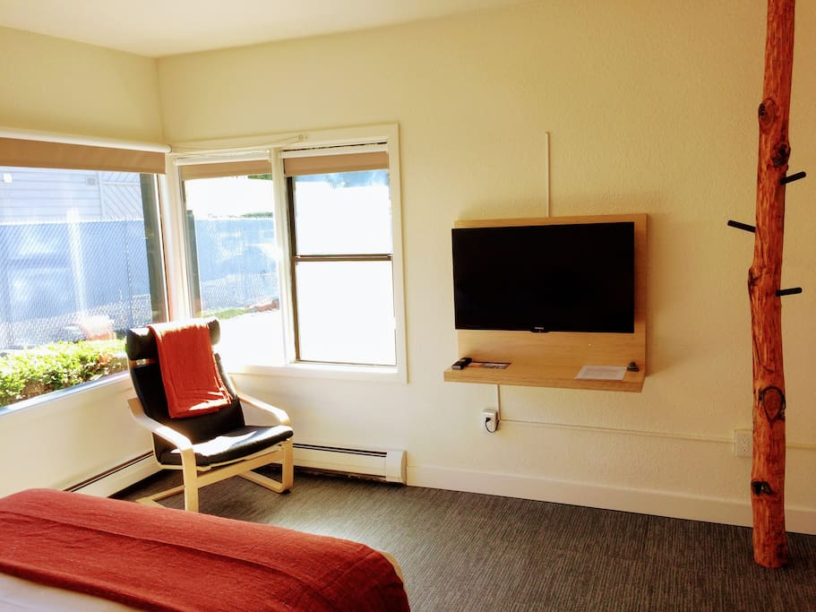 Flat screen TV with cable, a window nook, and a red alder clothing rack.