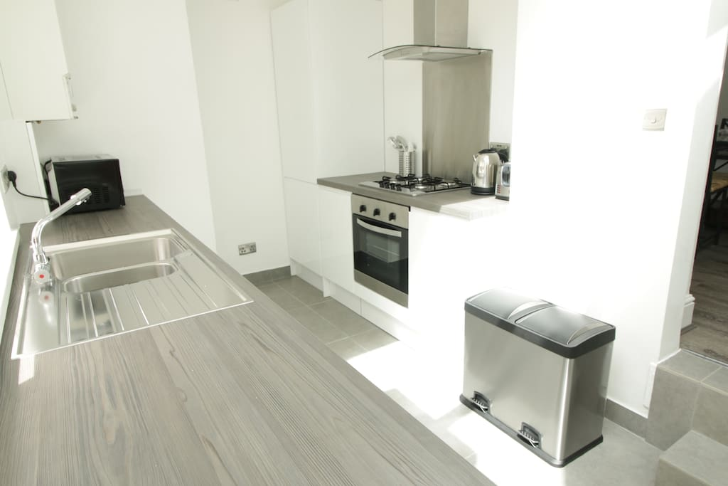 A fresh modern kitchen with all the essentials. Has door which goes out to the yard.