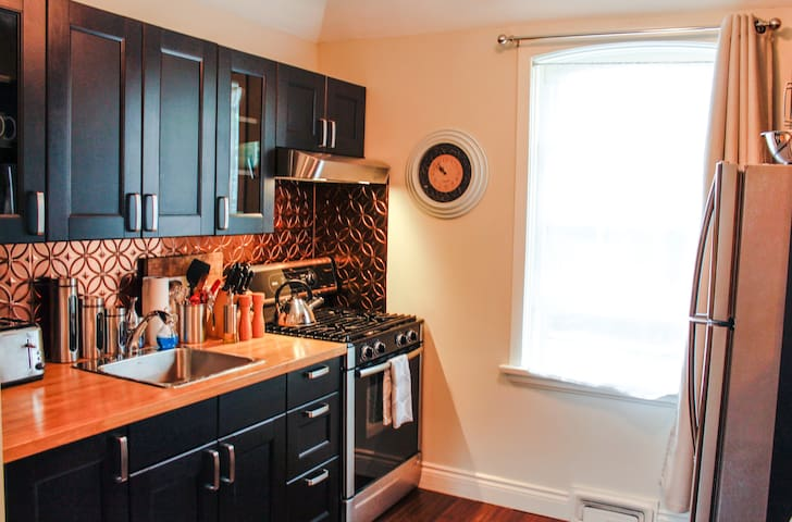 Contemporary Kitchen with Bamboo Countertop & Copper Tile Backsplash.
