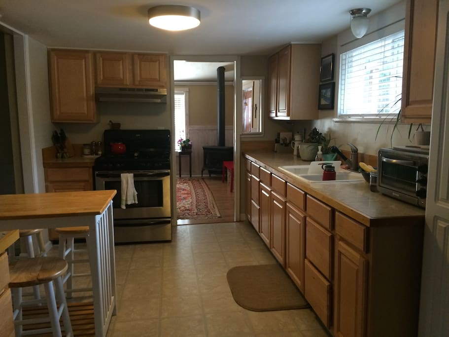 Kitchen with small dining table. Full sized fridge, gas stove & range, dishwasher, toaster oven and other small appliances. No coffee maker, but we do have a French press.