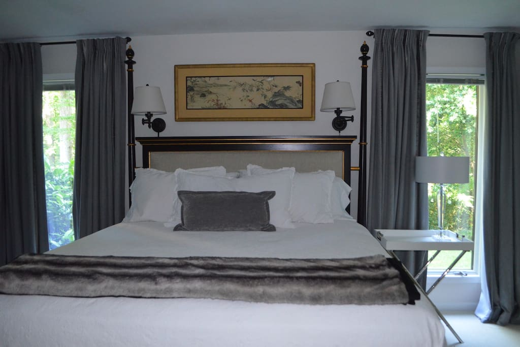 King bed with upholstered headboard; windows have blinds and black-out curtains