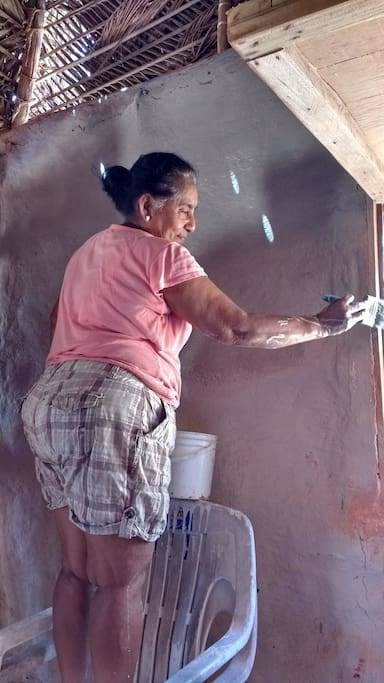 Esthela paints the adobe walls with a clay mixture that she collects in nearby Tehua.