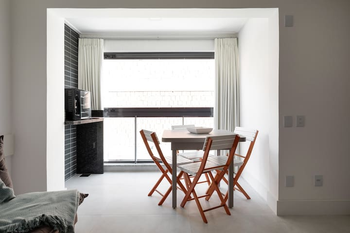 Sala com ambiente para jantar e churrasqueira elétrica