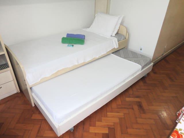 Sala com duas camas de solteiro, sofá cama que vira colchão de casal, rede de praia e mesa de jantar.