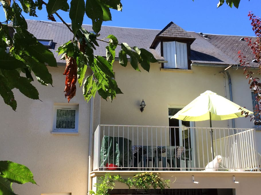 La cuisine donne sur une grande terrasse avec vue sur le jardin arboré.
