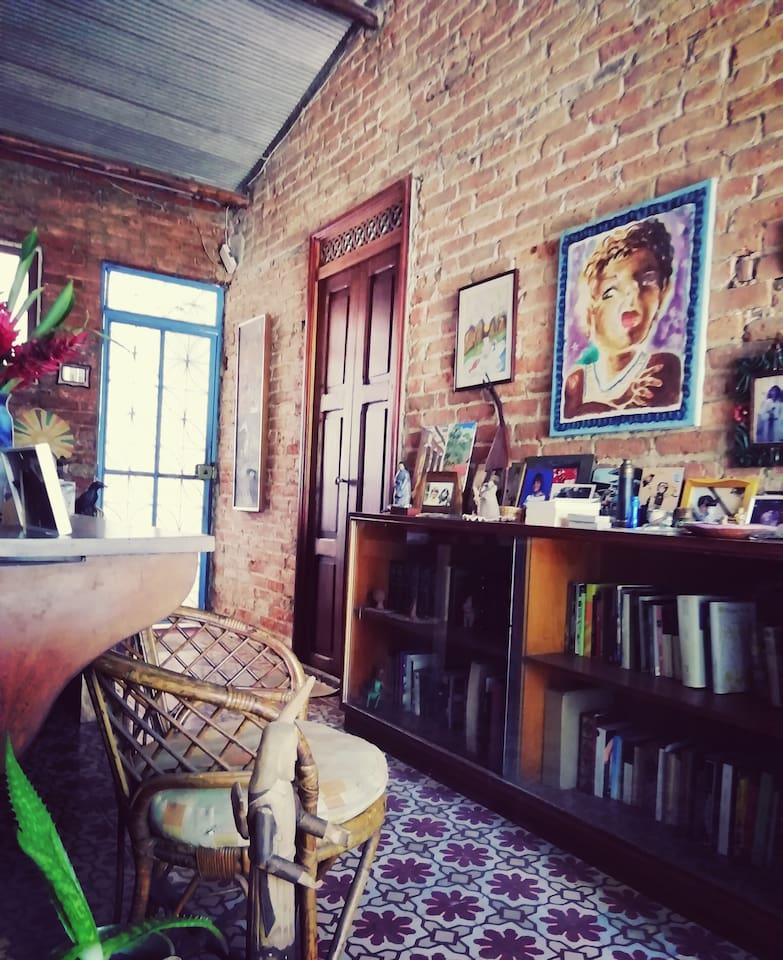 Sala común para compartir. Ambiente con libros, artesanías venezolanas y pinturas. Para conversar, tomar té o café.