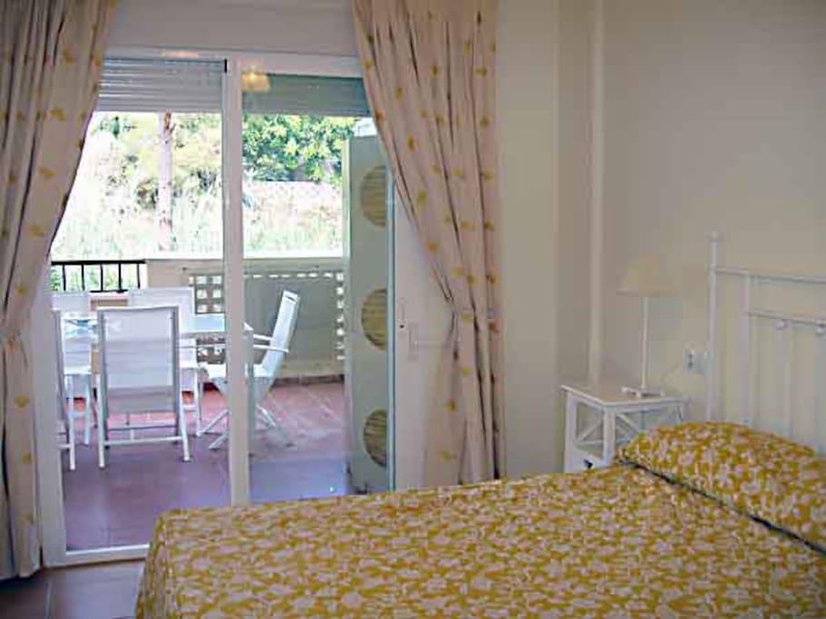 Amplio dormitorio con cama de matrimonio y dos armarios empotrados con cajoneras y salida a la terraza. Aire acondicionado. Tv de plasma