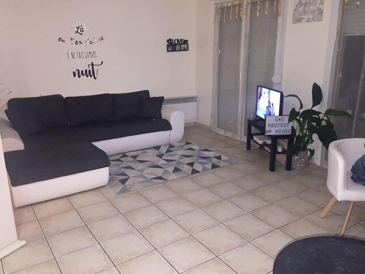 Un grand salon avec un grand canapé d'angle convertible 2 à 3 places et un grand balcon accessible