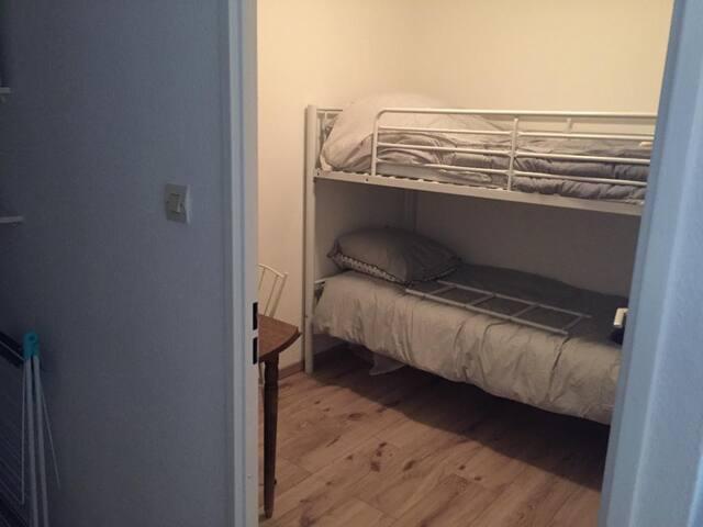 La seconde chambre avec lit superposé et coin table.