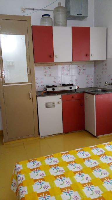 Cupboards, cabinets, stove with gas cylinder, & sink
