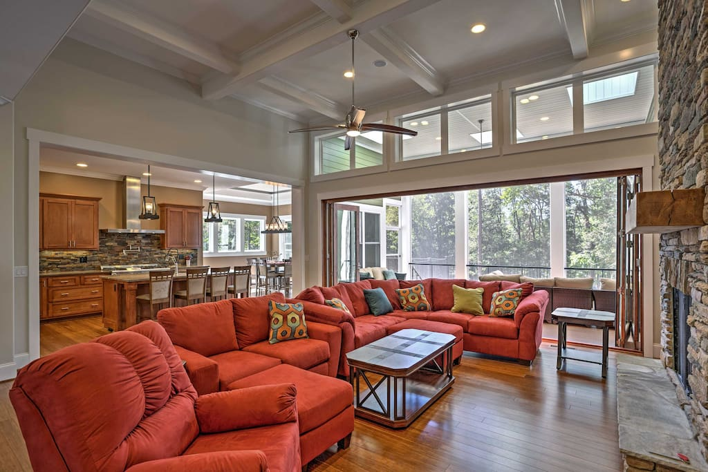 As soon as you open the front door, you'll be greeted by the Great Room, with cozy couches and a 2-story floor-to ceiling stone fireplace.