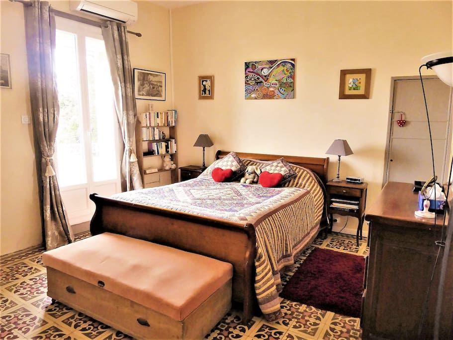 Spacious double bedroom with curtains, electric shutter, ceiling fan and air conditioning unit
