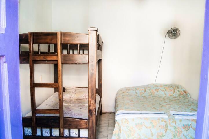 Habitacion amplia para 5 personas con ventilador y baño al frente con agua caliente.