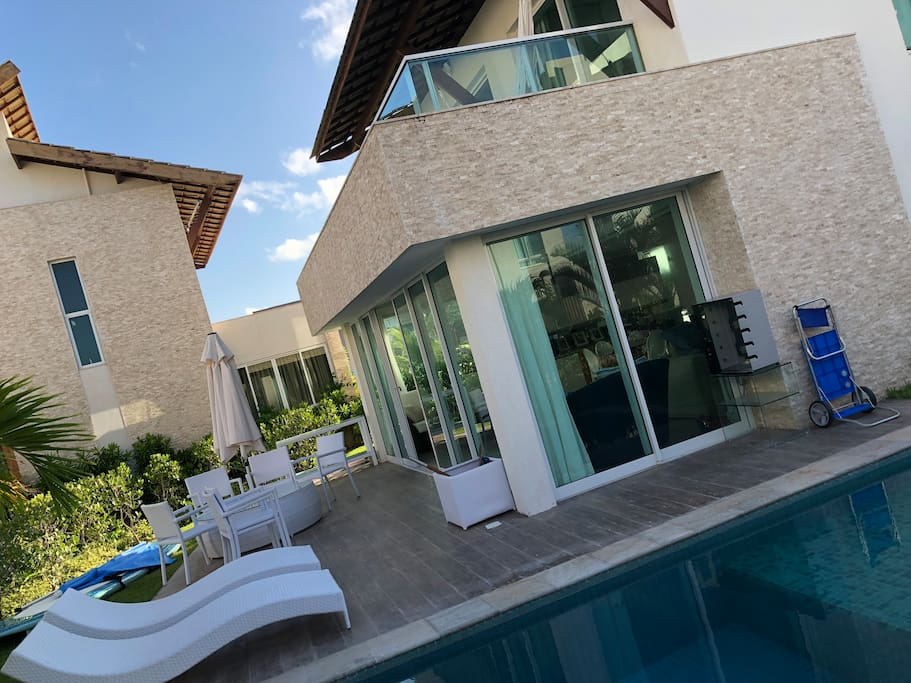 Varanda externa com piscina e churrasqueira elétrica