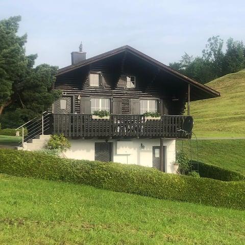 Klein huis in de natuur, uitzicht op de bergen en het meer