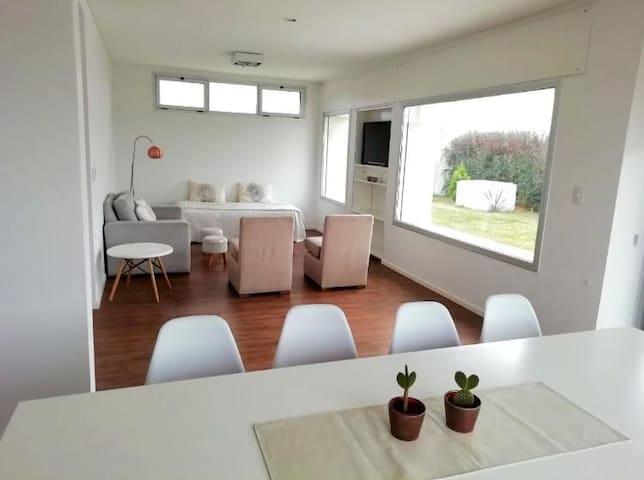 Comedor con sillones de 2 plazas, 2 butacas y cama funcional  Con TV smart y amplios ventanales al jardín y la pileta