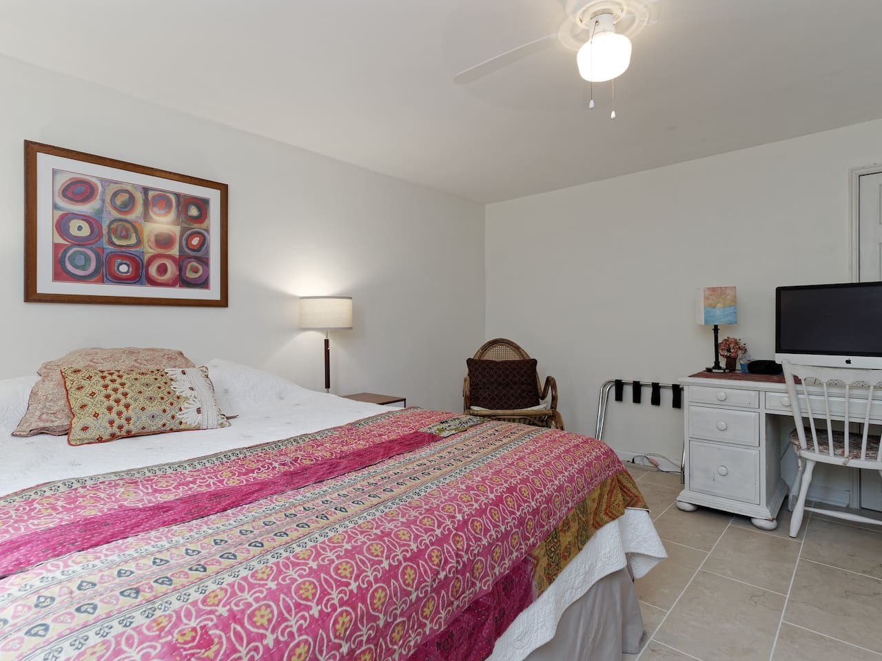 Welcome to a dark, quiet, comfortable bedroom! Queen-sized bed, rocker, ceiling fan, luggage rack, desk, PC with WiFi, books, brightly lit with LD lights, plus more, in the bedroom.