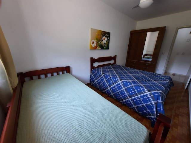 Quarto com uma cama de casal e uma bicama.